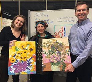 Katie (center) with two of her paintings, held by Liz Powers and her brother, Spencer.